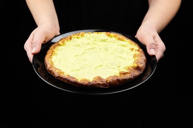 Gekochtes omelett aus hühnereiern in weiblichen händen auf schwarzem teller