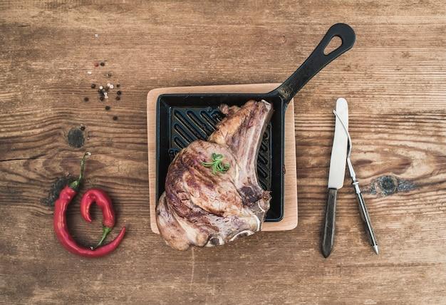 Gekochtes rib-eye-steak mit gewürzen, rotem chili, rosmarin und vintage-tafelsilber in einer pfanne