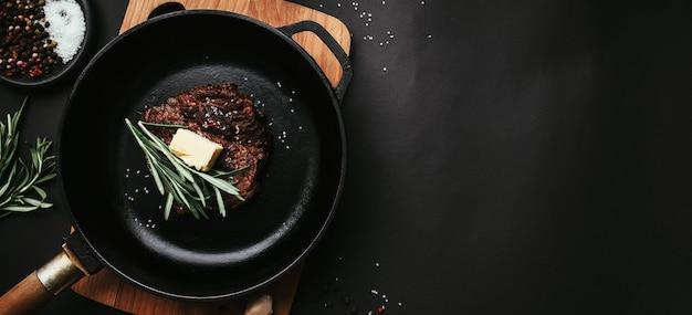 Gekochtes ribeye-steak auf gusseiserner pfanne und brett mit pfeffer, rosmarin, salz, knoblauch, butter auf schwarzem hintergrund. hochwertiges foto