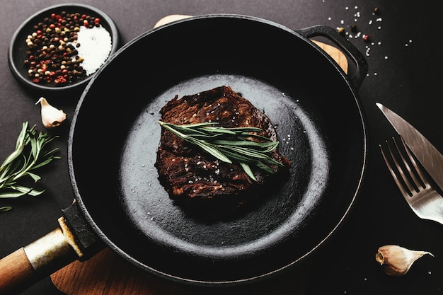 Gekochtes ribeye-steak auf gusseiserner pfanne und brett mit pfeffer, rosmarin, salz, knoblauch, messer, gabel, butter auf schwarzem hintergrund