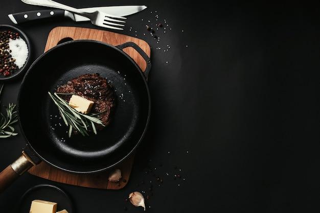 Gekochtes ribeye-steak auf gusseiserner pfanne und brett, rosmarin, messer, gabel, butter