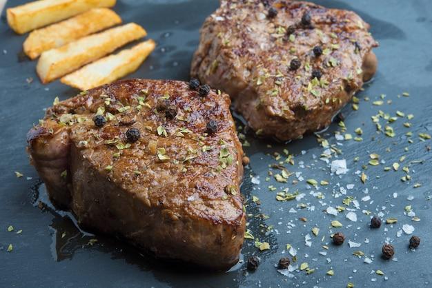 Gekochtes rindfleisch-chateaubriand-steak mit kartoffelchips auf platte