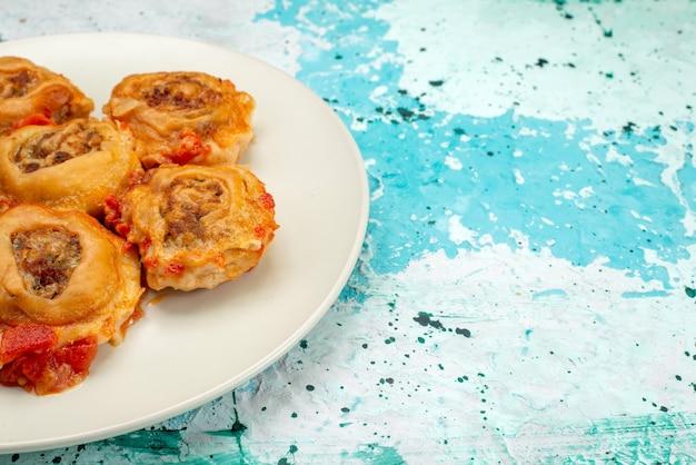 Gekochtes teigmehl mit hackfleisch in weißem teller auf hellblauem schreibtisch, teigmehl essen fleisch