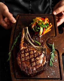 Gekochtes tomahawk long bone ribeye steak auf einem servierbrett