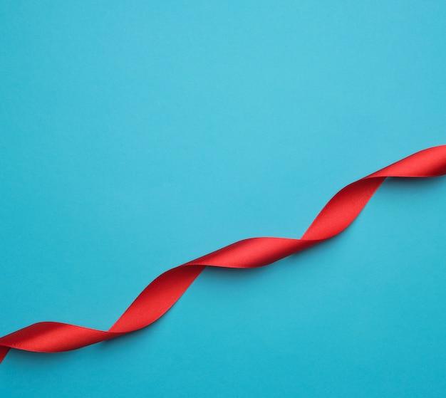Gekräuseltes rotes satinband auf blauem hintergrund