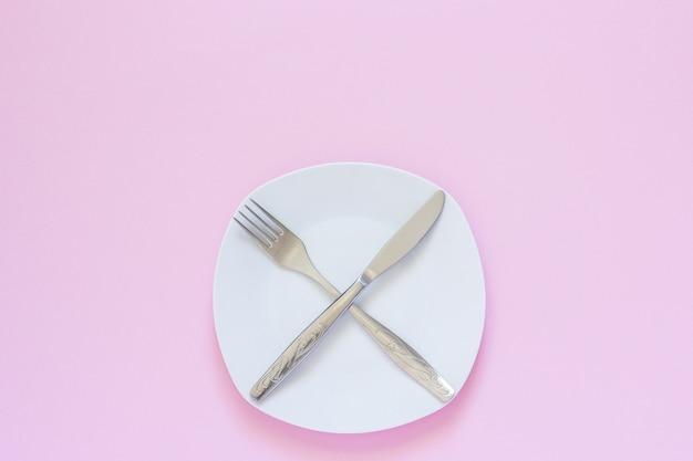 Gekreuzte gabel und messer auf weißer platte auf rosa hintergrund.