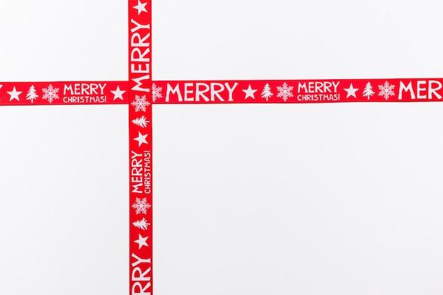 Gekreuzte rote bänder, die frohe weihnachten sagen