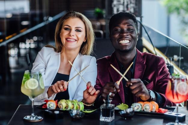 Gekreuzte stäbchen. zwei glückliche, junge freunde essen zusammen sushi-rollen im café.
