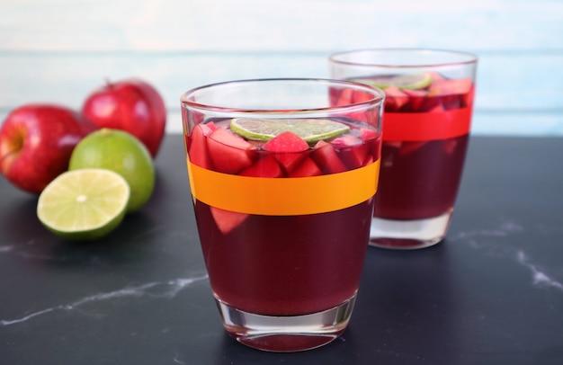Gekühlte rotwein-sangria auf dem tisch mit verschwommenen frischen früchten im hintergrund