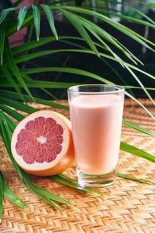 Gekühlte sommergetränke mit frischem rosa saft mit halber frucht auf weidenkorb mit blättern