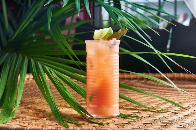 Gekühlte sommergetränke mit frischer mango, passionsfruchtsaft auf korbtisch mit blättern
