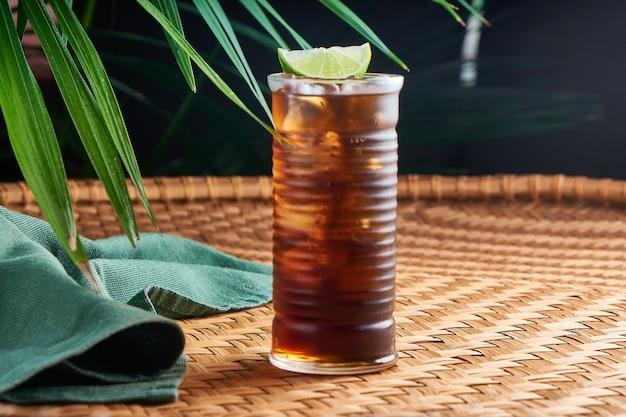 Gekühlte sommergetränke mit rum und cola auf einem korbtisch mit blättern