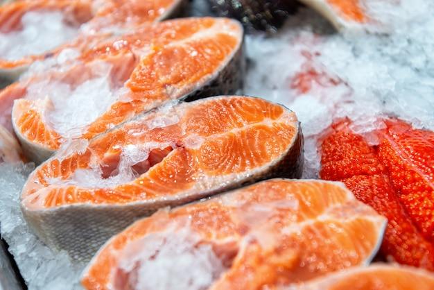 Gekühlte steaks von rotem fisch. fischstücke liegen auf eis.