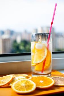 Gekühltes erfrischungsgetränk mit einem strohhalm mit orangenscheiben auf dem hintergrund der stadt