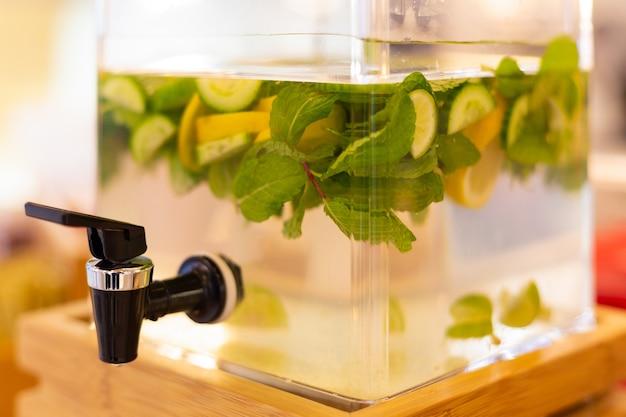 Gekühltes limetten-zitronen-getränk mit zucker in einer großen glasschüssel