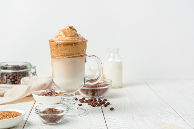 Gekühltes milchdessert mit kaffee und geschlagenem schaum auf einer weißen wand dalgon-kaffee. horizontale ansicht, kopienraum.
