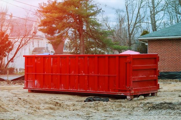 Geladener müllcontainer in der nähe einer baustelle, hausrenovierung