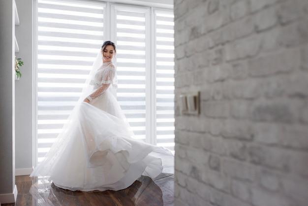 Gelächelte hübsche braut dreht sich im zimmer nahe weißer backsteinmauer um, gekleidet in modisches kleid, hochzeitsmode