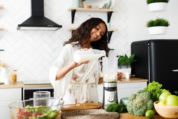 Gelächelte hübsche mulattefrau gießt milch in die mischmaschine nahe der tabelle mit frischgemüse auf der weißen modernen küche, die im nachtzeug mit dem losen haar gekleidet wird