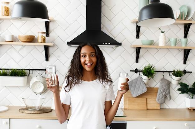 Gelächelte mulattefrau hält leeres glas und glas mit milch nahe dem küchenschreibtisch auf der modernen weißen küche, die im weißen t-shirt gekleidet wird