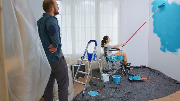 Gelähmte frau malerei wand mit walzenbürste auf rollstuhl sitzend. behinderte, behinderte, kranke und bewegungsunfähige frau, die bei der renovierung von wohnungen und beim hausbau hilft, während sie renovieren und im