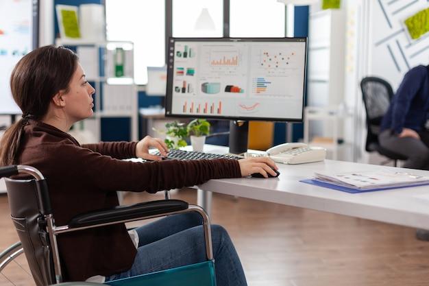 Gelähmte geschäftsfrau im rollstuhl, die marketingstrategie tippt, die im unternehmen arbeitet