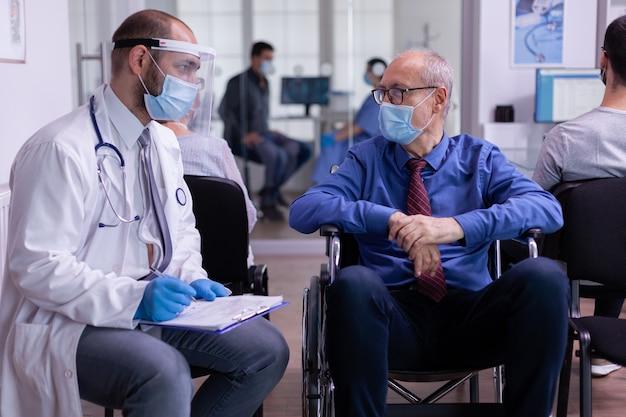 Gelähmter älterer mann mit gesichtsmaske, der im rollstuhl im empfangsbereich sitzt und mit spezialisten spricht...