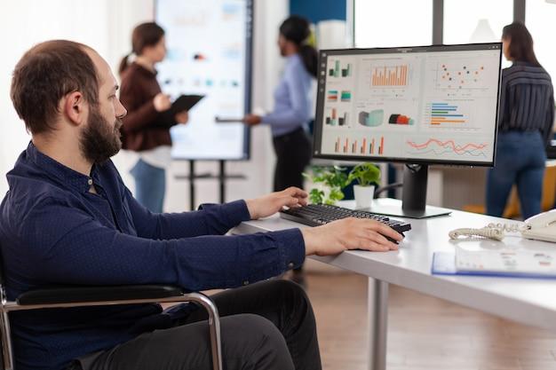 Gelähmter behinderter geschäftsmann, der managementstrategie auf dem computer eingibt