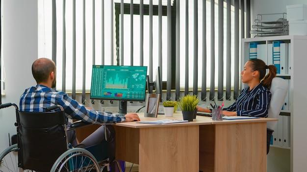 Gelähmter finanzarbeiter, der im rollstuhl sitzt, immobilisiert, analysiert wirtschaftsstatistiken des unternehmens im geschäftsbüro und diskutiert mit kollegen. behinderter geschäftsmann mit moderner technologie
