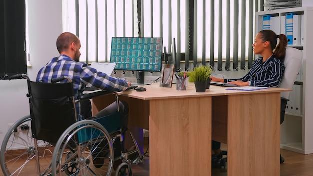 Gelähmter finanzexperte, der im rollstuhl sitzt und wirtschaftsstatistiken des unternehmens im geschäftsbüro analysiert und mit der managerin diskutiert. behinderter, immobilisierter geschäftsmann mit moderner technologie.