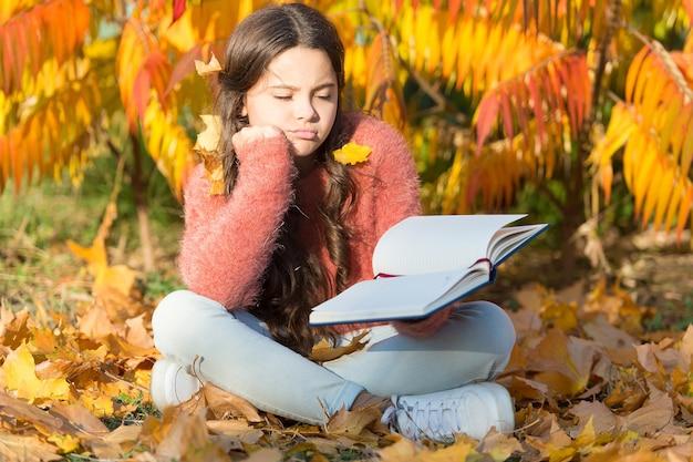 Gelangweilt und müde. kleines kind genießt das lernen im hinterhof oder im park. kinderstudie mit buch. selbstbildungskonzept. kind viel spaß beim lesen. schulmädchen-studie. lerne jeden tag. mädchen las buch herbsttag.