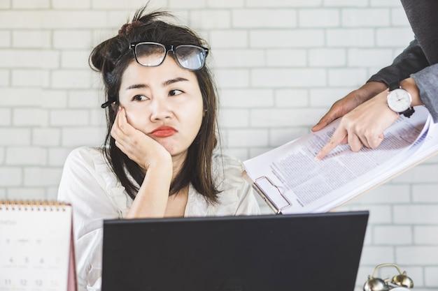 Gelangweilte asiatische arbeitnehmerin ignorieren chef im büro
