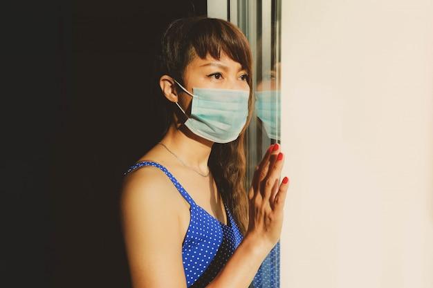 Gelangweilte asiatische frau, die gesichtsmaske trägt, die aus fenster während quarantäne zu hause schaut