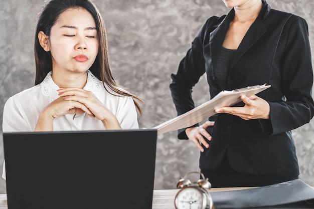 Gelangweilte asiatische mitarbeiterin ignoriert nervigen chef