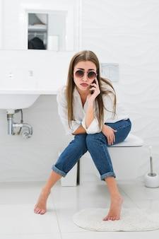 Gelangweilte frau, die am telefon spricht, während sie auf der toilette sitzt