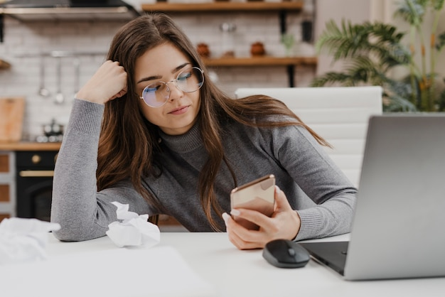 Gelangweilte frau, die ihr telefon überprüft, während sie von zu hause aus arbeitet