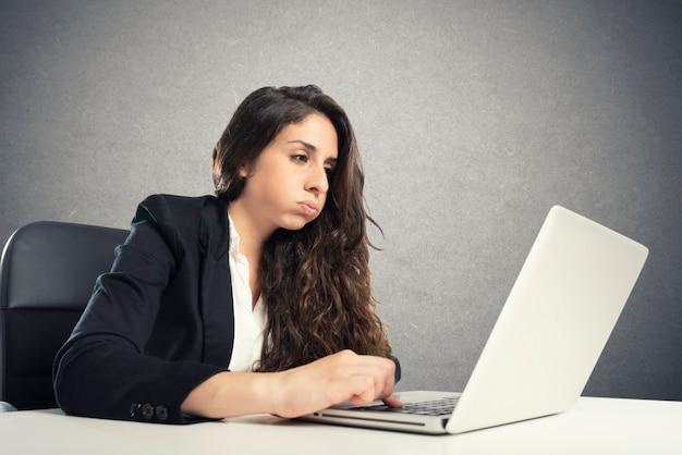 Gelangweilte frau schnaubt im büro, während sie am laptop arbeitet