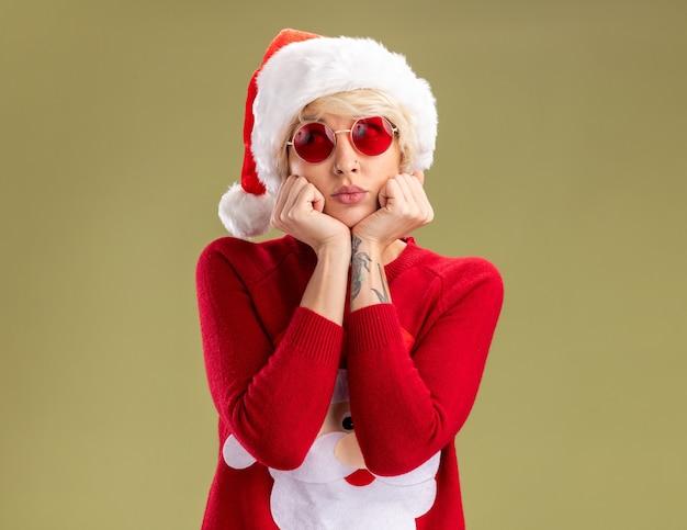 Gelangweilte junge blonde frau, die weihnachtsmütze und weihnachtsmann-weihnachtspullover des weihnachtsmanns mit brille trägt, hält hände unter kinn, das seite lokalisiert auf olivgrünem hintergrund betrachtet
