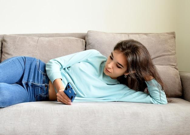 Gelangweilte junge frau, die auf dem sofa liegt und smartphone rollt