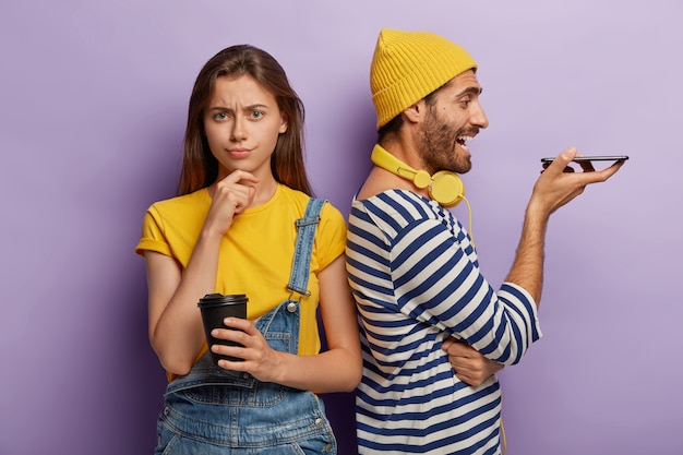Gelangweilte junge frau trinkt kaffee zum mitnehmen, verwirrt von freunden ignorieren, mann in gestreiftem pullover und gelbem hut steht zurück zu freundin