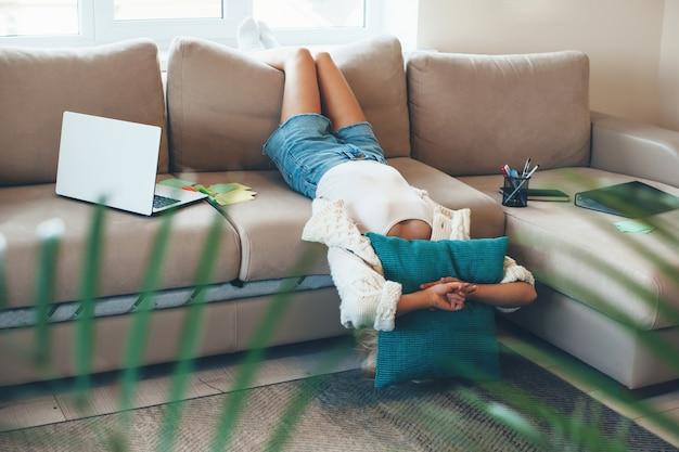 Gelangweilte kaukasische frau, die auf sofa mit einem kissen liegt, nachdem sie online-lektionen mit laptop getan hat