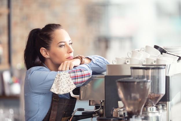 Gelangweilte kellnerin lehnt arbeitslos an der kaffeemaschine und hält gesichtsmaske in der hand.