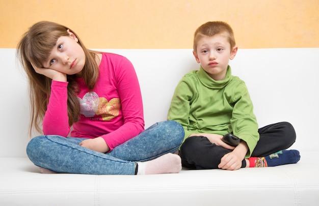 Gelangweilte kinder sitzen auf der couch