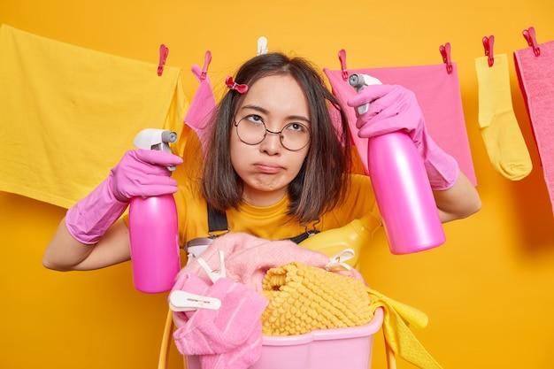 Gelangweilte, müde, erschöpfte asiatische hausmeisterin hält zwei flaschen reinigungsmittel, die damit beschäftigt sind, wäsche zu waschen und das haus zu reinigen