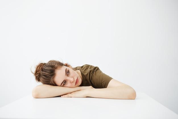 Gelangweilte müde langweilige junge studentin mit brötchen, das am tisch über weißem hintergrund sitzt.