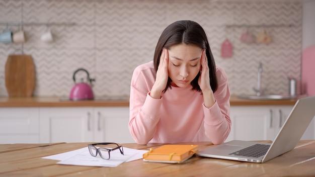 Gelangweilte, schläfrige asiatische dame, die am schreibtisch mit laptop sitzt und den kopf auf der hand ruht hält am arbeitsplatz schlafen müde junge frau, die sich schläfrig faul und unmotiviert fühlt