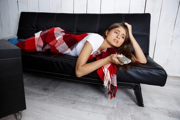 Gelangweilte schöne frau, die fernsieht, zu hause auf sofa liegend.