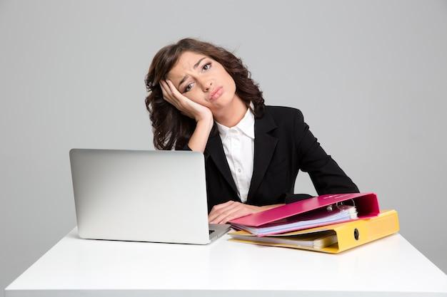 Gelangweilte traurige depressive lockige hübsche junge frau, die laptop benutzt und mit dokumenten in bunten mappen arbeitet working