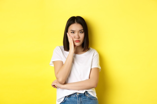 Gelangweilte und genervte asiatische frau, die es leid ist zuzuhören, skeptisch in die kamera schaut und über gelb steht