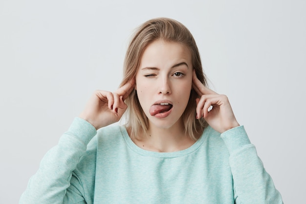 Gelangweilte und genervte junge blonde frau, die die stirn runzelt und die ohren mit den fingern verstopft, kann keinen lärm ertragen, die stressige situation ignorieren und die zunge herausstrecken. negative menschliche emotionen